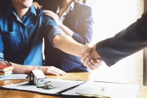 Picture of an attorney shaking hands with clients who are closing on a house.
