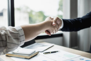 Picture of two people shaking hands in an office.